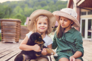 two cute little sisters hugging dog puppy. friendship and care concept