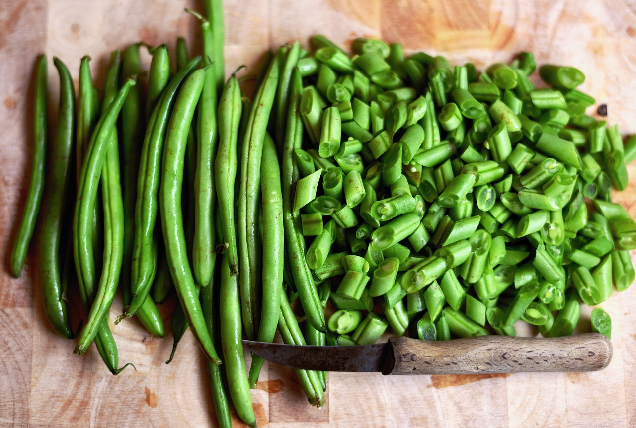 whole and chopped green beans with knife