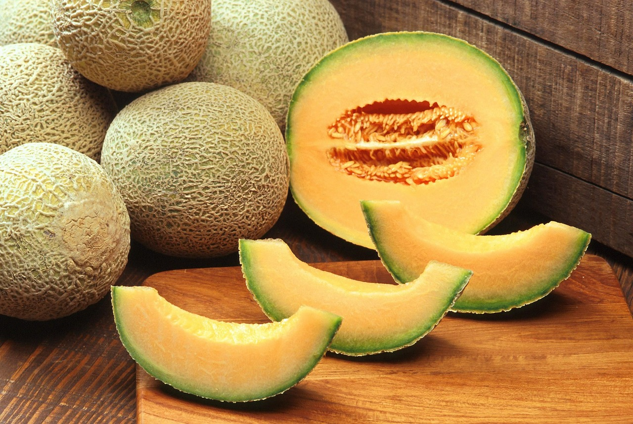 whole cantaloupes and slices on cutting board